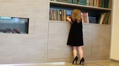 Girl in adult shoes near bookcase business center Stock Footage