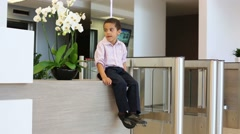 Biracial boy sits next to glass turnstile in business center Stock Footage