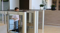 mulatto boy passes through glass turnstile in business center - stock footage