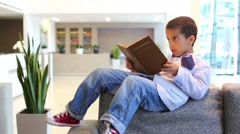 Curly boy lying on sofa with book in business center Stock Footage