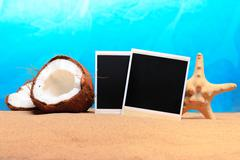Chopped coconut and photoframe on the sand Stock Photos