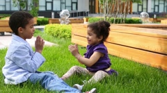 Brother and sister sit on grass and clap each other hands Stock Footage