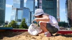 Little girl with white bag plays in sandbox near skyscrapers Stock Footage