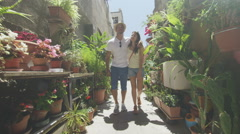 Attractive couple walking through narrow city alley with lots of plants Stock Footage