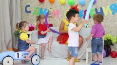 Kids look at holiday representative inflating balloon by pump Stock Footage