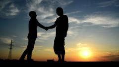 Man meeting woman on the street in sunset and greeting her wind a warm handshake Stock Footage