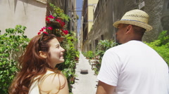 Attractive couple walking through narrow city alley with lots of plants - stock footage