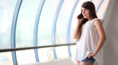 Pretty girl in white blouse talks phone in long blue gallery Stock Footage