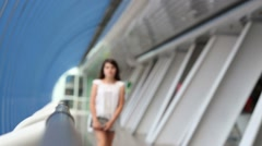 Pretty girl with tablet pc walks in long blue gallery Stock Footage
