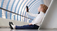 Red hair little girl sits on floor and holds black cell phone Stock Footage