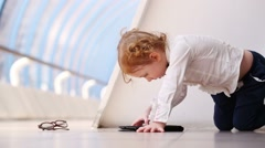 Little barefoot girl sits and plays with tablet pc in gallery Stock Footage
