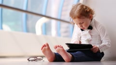 Little barefoot girl sits on floor with tablet pc in gallery Stock Footage