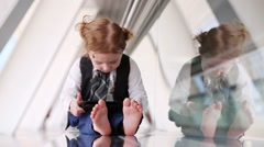 Little girl in tie sits on floor in gallery near glass wall Stock Footage