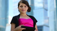 Beautiful girl in dress works with tablet pc near skyscrapers Stock Footage