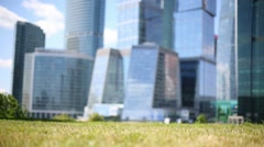 Little cute girl runs on grass near skyscrapers at sunny day Stock Footage