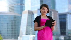Smiling girl works with tablet pc stands near skyscrapers Stock Footage