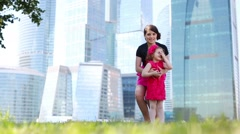 Beautiful girl hugs and twists little girl on grass Stock Footage