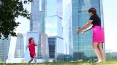 Beautiful girl circles little girl in red near blue skyscrapers Stock Footage