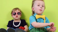 Little boy and girl sit near bright green wall, focus on boy Stock Footage