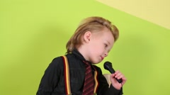 Boy in bright clothes sings into microphone near green wall Stock Footage