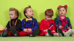 Two boys and two girls sit near bright wall in studio Stock Footage