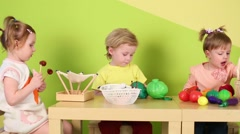 Two boys and girl play with plastic vegetables and other toys Stock Footage