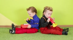 Boys sit back to back and play on toy trumpet and metallophone Stock Footage