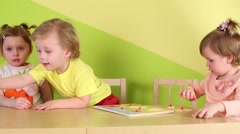 Four children play with wooden toys, sitting at table Stock Footage
