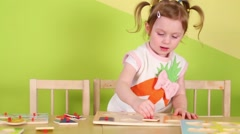 Girl with pigtails puts wooden geometric shapes on board Stock Footage