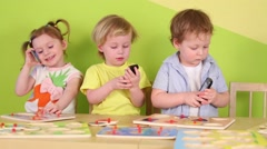Three children with phones in hands at table with toys Stock Footage