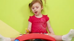 Girl with pigtails plays on xylophone near green wall Stock Footage