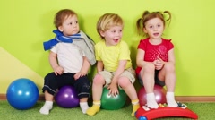 Two boys and girl with metallophone sit on balls in bright room Stock Footage