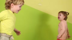 Little girl and boy jump and run among falling soap bubbles Stock Footage