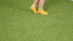 Feet in socks of two little running kids on floor with carpet - stock footage