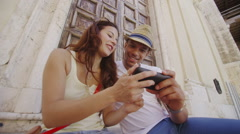 Attractive couple with mobile phone, sightseeing and having fun in city - stock footage