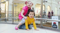 Little girl and boy play on floor in big mall. Girl saddled boy Stock Footage