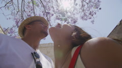 Attractive couple standing under tree in the summertime Stock Footage