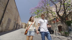 Happy attractive couple walking through city street in the summertime - stock footage