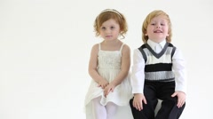 Little smiling girl and boy sit on white big cube in studio Stock Footage