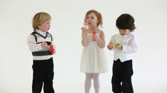 Little happy girl and two boys blow bubbles in white studio Stock Footage