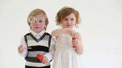 Little smiling girl and boy blow bubbles in white studio Stock Footage