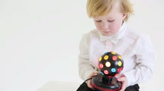 Little blond boy holds ball-shaped lamp in white studio Stock Footage