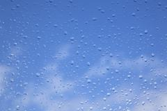 Rain drops on window pane and blue sky Stock Photos