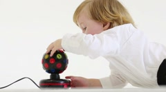Little blond boy lies on floor and looks at ball-shaped lamp Stock Footage