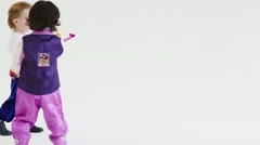 Two handsome boys in folk costumes play with party blower Stock Footage