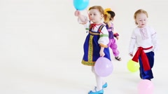 Little girl and two boys in folk costumes play with balloons Stock Footage