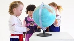 Two little boys and girl in folk costumes looks at world globe Stock Footage
