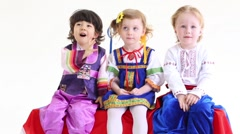 Little boys and girl in folk costumes sits with sticks Stock Footage