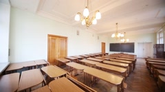 Empty small classroom with wooden desks and chandeliers Stock Footage