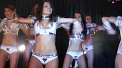 Six beautiful showgirls in white shine costumes dance on stage Stock Footage